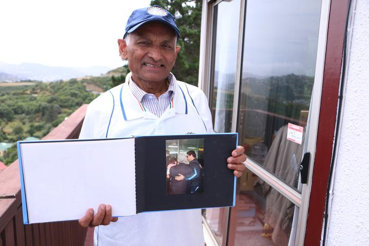Nanubhai Ranchhod holds his photo album with his prized photo of him and legendary cricketer Sachin Tendulkar hugging at the airport.