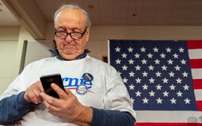 A supporter checks his phone as he attends the Caucus Night Celebration event for Democratic presidential candidate Vermont Senator Bernie Sanders in Des Moines, Iowa, on February 3, 2020.