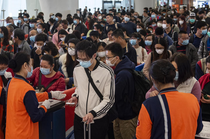 People cover their faces with sanitary masks at an airport in Hong Kong, China.