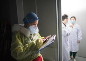 Nurse Sun Chun reads medical records at a hospital in Wuhan, yesterday.