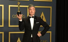 "New Zealand director Taika Waititi poses in the press room with the Oscar for Best Adapted Screenplay for ""Jojo Rabbit""."
