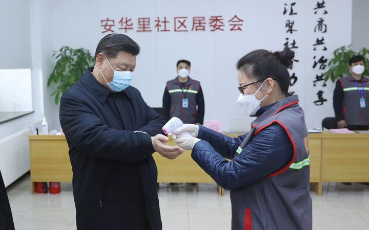 Chinese President Xi Jinping wearing a protective facemask as a health official checks his body temperature during an inspection of the novel coronavirus pneumonia prevention and control work at the Anhuali Community in Beijing.
