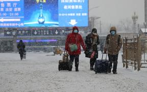 People wearing masks walk the Beijing Station area in the snow in Beijing on 6 February 2020.