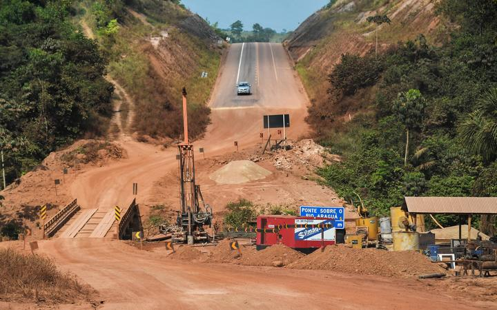 A pickup truck drives near a of the Trans-Amazonian highway (BR230) under construction, near Ruropolis, Para state, Brazil, in the Amazon rainforest, on September 7, 2019.