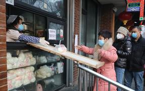 Shop staff uses a board to hand mantous, Chinese steamed bun, to customer in Beijing on February 11, 2020.