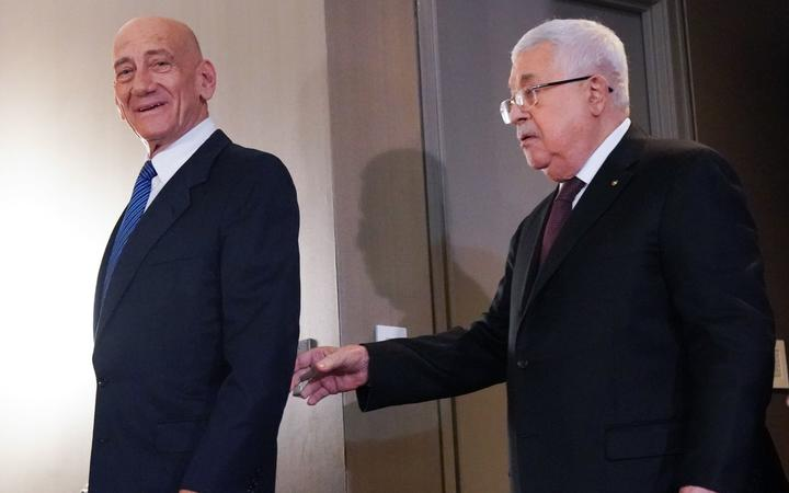 Palestinian president Mahmud Abbas (R) and Former Israeli Prime Minister, Ehud Olmert, arrive for a press conference on US President Donald Trump's Mideast peace plan on February 11, 2020 in New York. -