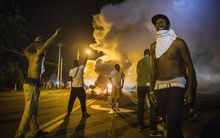 Demonstrators react to tear gas fired by police.