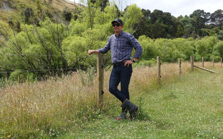 Yong farmer in cap stands by new fence r