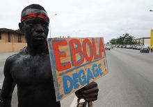 "A member of an Ivory Coast artist group hold a placard reading ""Ebola, go away""."