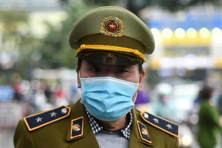 A Vietnamese policeman wearing a protective facemask stands guard at a make-shift distribution centre for free facemasks amid concerns of the novel coronavirus outbreak, in Hanoi.