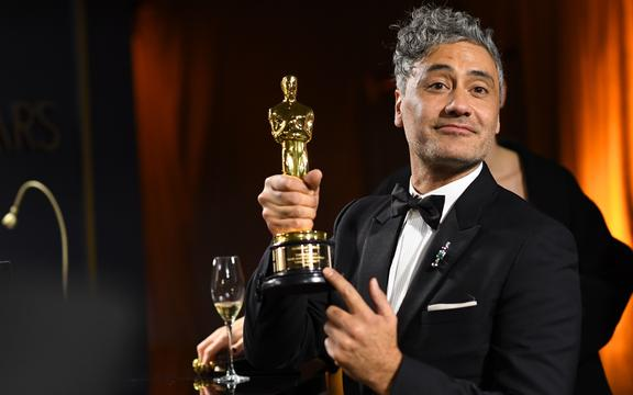 "New Zealand director/actor Taika Waititi (R) waits as his award for Best Adapted Screenplay for ""Jojo Rabbit"" is engraved as he attends the 92nd Oscars Governors Ball at the Hollywood & Highland Center in Hollywood, California on February 9, 2020. (Photo by VALERIE MACON / AFP)"