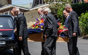 Mike Moore's casket is carried into his funeral service in Auckland.