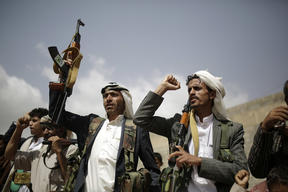 Houthi rebel fighters hold their weapons and shout slogans during a gathering aimed at mobilizing more fighters before heading to battlefronts.