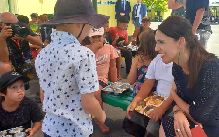 Prime Minister Jacinda Ardern talks to students receiving a free lunch at Flaxmere Primary School.