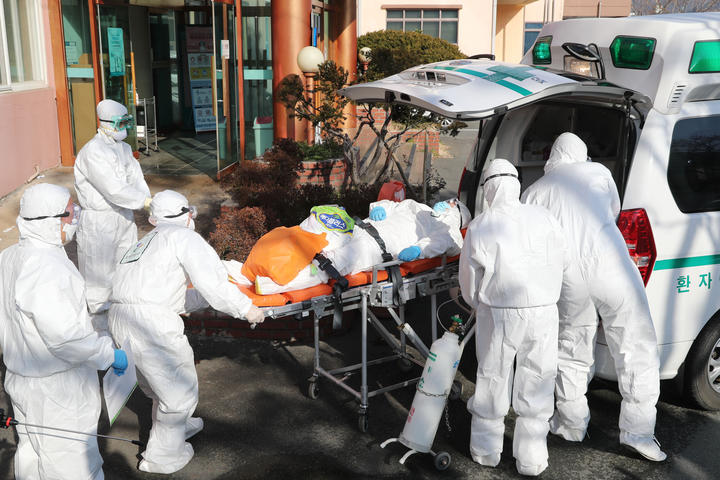 Medical workers wearing protective gear transfer a suspected coronavirus patient  to another hospital from Daenam Hospital where a total of 16 infections have now been identified.