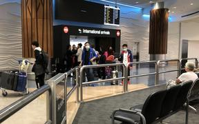 Passengers arriving at Auckland Airport in January 2020 when public health staff began giving out coronavirus information.