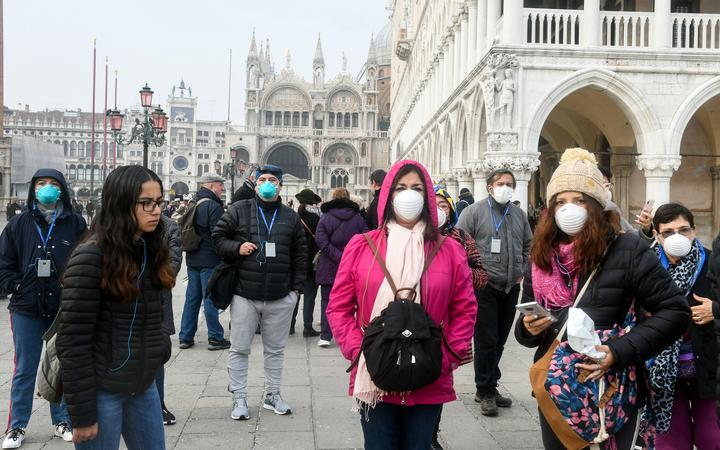 Tourists wearing protective masks visit Venice on 25 February 2020, during the usual period of the Carnival festivities which were cancelled after an outbreak of the Covid-19 coronavirus.