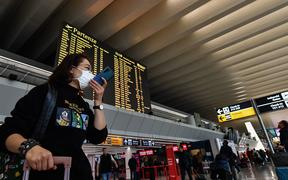 A passenger wearing a respiratory mask speaks on her smartphone by the departures board at Rome's Fiumicino airport.