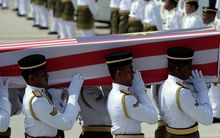 Soldiers carry a coffin with the remains of a Malaysian victim of the Malaysia Airlines flight MH17 crash during a ceremony at Kuala Lumpur International Airport.