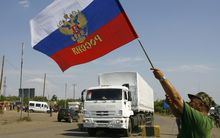 A Russian national flag is waved as  trucks cross the Ukrainian border at the Izvarino custom control checkpoint.