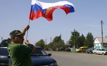 A local resident holds a Russian national flag as lorries, part of a Russian humanitarian convoy, cross the Ukrainian border on August 22, 2014.