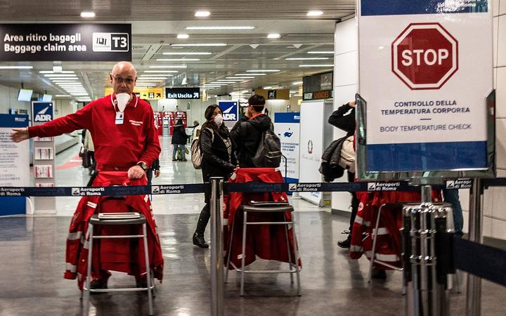 An airport staff directs passengers exiting an airplane that landed at Rome's Fiumicino airport from Paris on March 7, 2020 as part of body temperature screening procedures to prevent the spread of the new coronavirus.