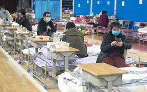 Patients rest at a makeshift hospital in Wuchang District of Wuhan, central China's Hubei Province, March 8, 2020. Patient numbers decreased as many are transferred or discharged. By Sunday afternoon, the hospital has admitted a total of 1124 patients. 116 of them are currently being treated.