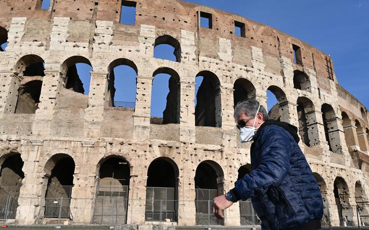 A man wearing a respiratory mask  walks past the closed Colosseum  in Rome on 10 March, 2020