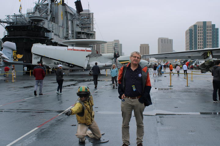 Leo Schepp standing in the very large hanger of the aircraft carrier Midway, that is now a floating museum in San Diego.