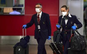 Crew members wearing face masks as a preventive measure against the spread of the Covid-19 coronavirus arrive at Ezeiza International Airport in Buenos Aires, on March 12, 2020.