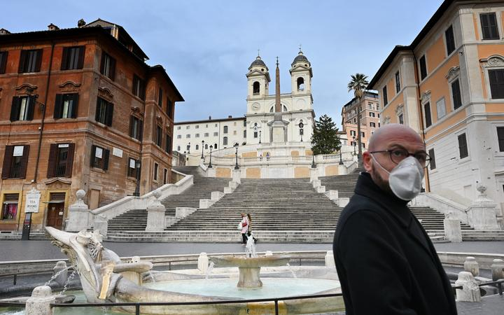 A man wearing a protection mask walks by the Spanish Steps at a deserted Piazza di Spagna in central Rome.