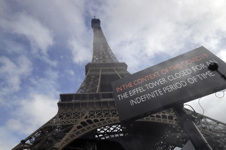 A picture taken on March 14, 2020 near the Eiffel tower in Paris shows a board informing of the monument's closure as a precaution against the coronavirus.