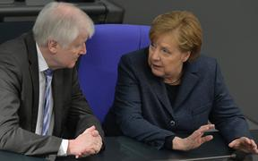 German Interior Minister Horst Seehofer chats with Chancellor Angela Merkel during a session of the German lower house of parliament Bundestag in Berlin on March 4, 2020.
