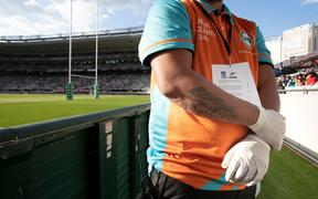 A security staff member wearing gloves during a Super Rugby match at Eden Park.
