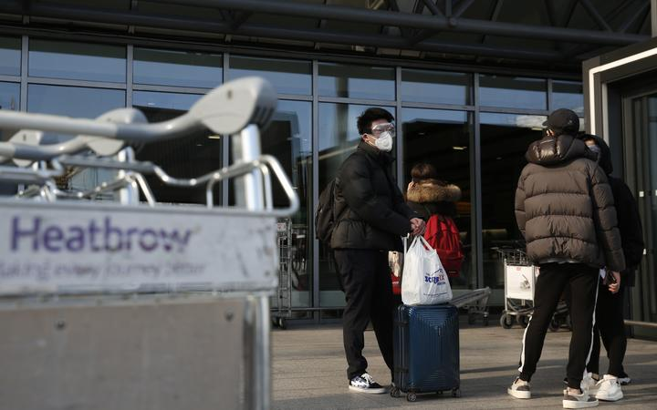 Travellers wearing a mask wait oustside an Heathrow's airport terminal, in west London, on March 16, 2020.