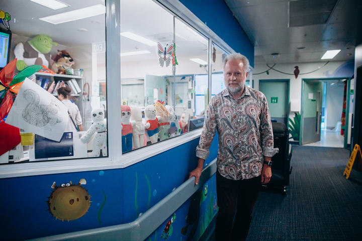 Man in paisely shirt stands new toys in a children's ward
