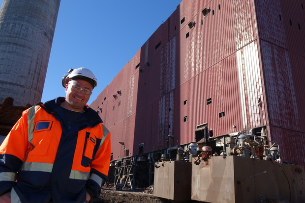 Nikau Contractors project manager John Paul Stil beside the New Plymouth Power Station boiler house which is to be completely demolished and the chimney that will remain standing.
