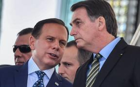 Brazilian President Jair Bolsonaro (R) listens to Sao Paulo's Governor Joao Doria while attending a military event in Sao Paulo, Brazil, on October 11, 2019.