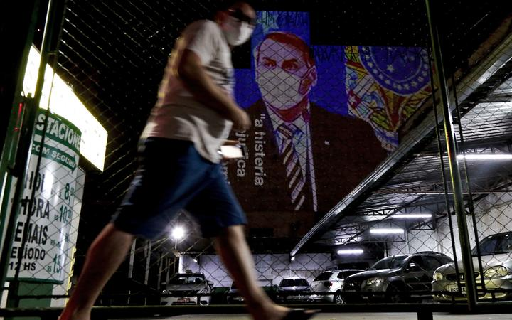 "An image of Brazil's President Jair Bolsonaro wearing a protective face mask and the phrase ""Hysteria Damages the Economy"" is projected on the wall of a building as a protest against the president regarding his handling of the coronavirus COVID-19 outbreak, in Sao Paulo, Brazil, March 21, 2020."