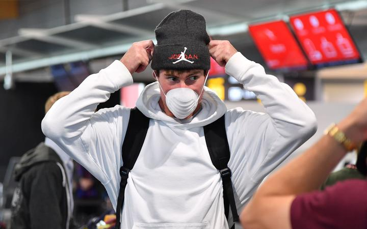 Phoenix's keeper Oliver Sail puts on a mask at Wellington airport as the team heads to Australia for the rest of the season.