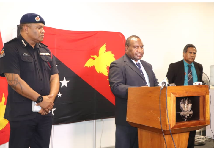 PNG prime minister James Marape (centre) announces provisions for the 14-day state of emergency beginning Tuesday 24 March, alongside police commissioner David Manning and health secretary Paison Dakulala.