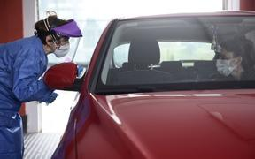 A health worker dressed in protective gear takes samples from a driver at a drive-through testing centre for the Covid-19 disease at Donostia Hospital in San Sebastian on 25 March .