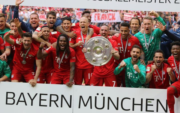 Bayern Munich's players and the team pose with the trophy after the German First division Bundesliga football match FC Bayern Munich v Eintracht Frankfurt in Munich, 2019.
