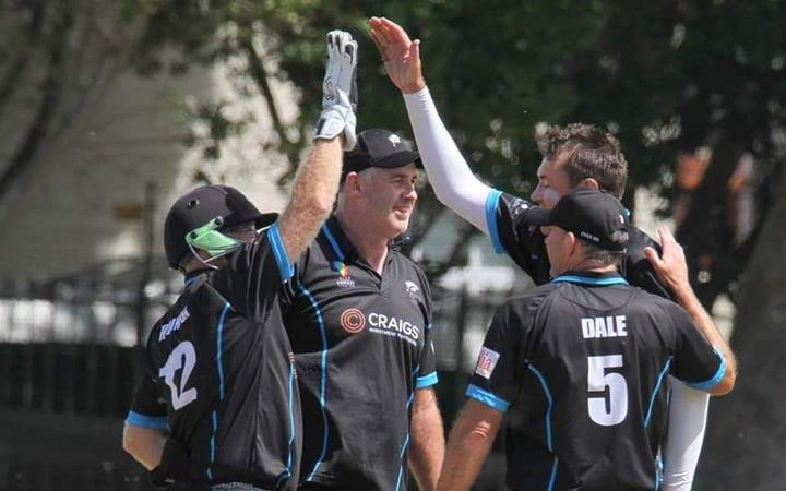 Stephen Hewson celebrates with teammates after taking a wicket in the over 50s Cricket World Cup in Cape Town, South Africa.
