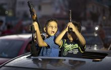Children hold up guns to celebrate the Gaza Strip ceasefire.
