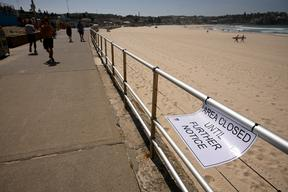 People walk past an empty Bondi Beach after authorities closed Sydney's most popular beach on March 22, 2020. Bondi Beach was closed after huge crowds flocked to the popular sunbathing spot despite a government ban on large gatherings due to the coronavirus pandemic.