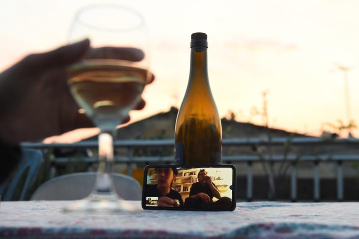 A woman drinks a glass of wine as she speaks and shares a drink with friends via a video call.
