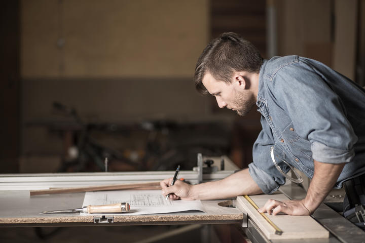 Carpenter looking at the plans, joiner, small business