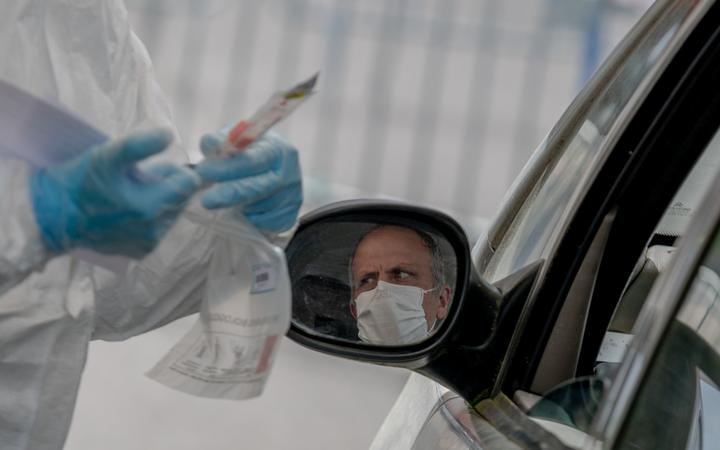 Biologists take samples by appointment from people with symptoms of Covid-19 without having to get out of their vehicles on April 6, 2020 in Saint-Nazaire, France.