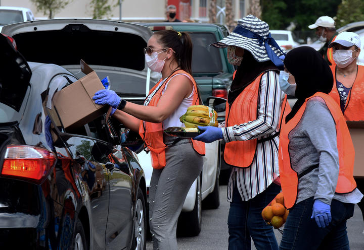 Volunteers distribute food to needy families during a drive-thru event on 9 April, Orlando, Florida. The food bank has seen record demand, due to job losses caused by the pandemic.